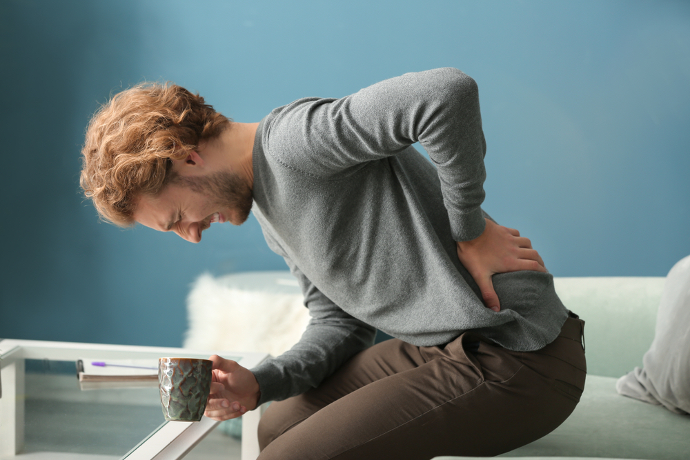 Man with coffee and back pain